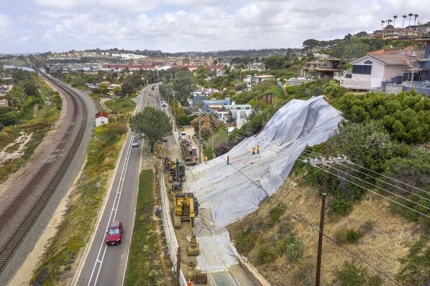 In this view looking north, sheets of plastic cover the bluff failure that sent tons of dirt onto the northbound lane of Jimmy Durante Boulevard.