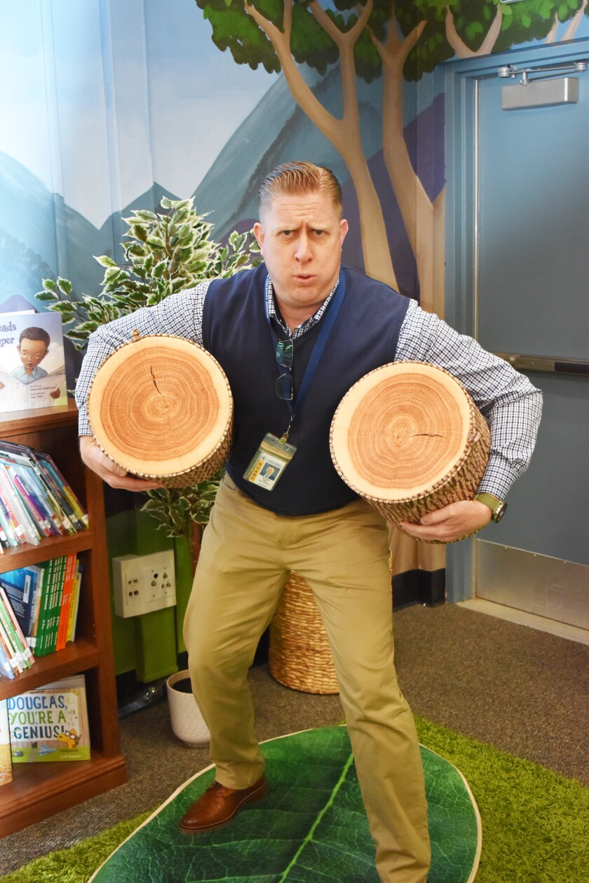 Poway Unified School District board member T.J. Zane hefts the log pillows in the new reading room.
