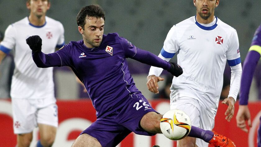 Fiorentina's Giuseppe Rossi, left, kicks the ball as Belenenses's Ricardo Dias watches him, during t