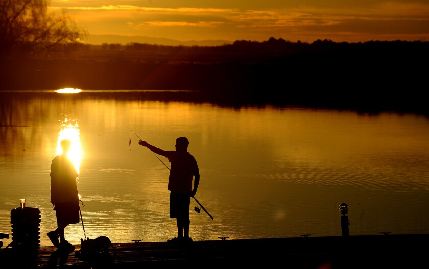 Two young men fish from a marina dock in the Sacramento-San Joaquin Delta. The State Water Resources Control Board has issued a draft cease-and-desist order against an irrigation district that diverts supplies from the delta's Old River.