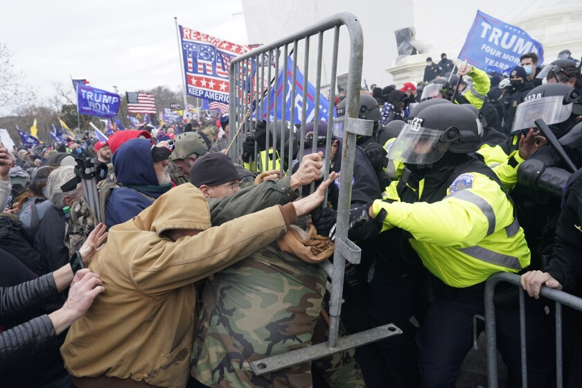 Insurrectionists attempt to force their way through a police barricade in front of the Capitol.