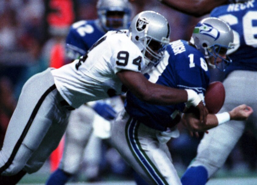 FILE - In this Oct. 18, 1992, file photo, Los Angeles Raiders' Anthony Smith (94) sacks Seattle Seahawks quarterback Stan Gelbaugh during the second quarter of an NFL football game in Seattle. Smith, a former defensive end with the Oakland and Los Angeles Raiders, has been found guilty Thursday, No