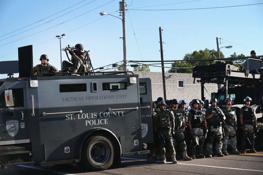 Police in riot gear stand with armored vehicle watching protesters in Ferguson, Mo., on Aug. 13.