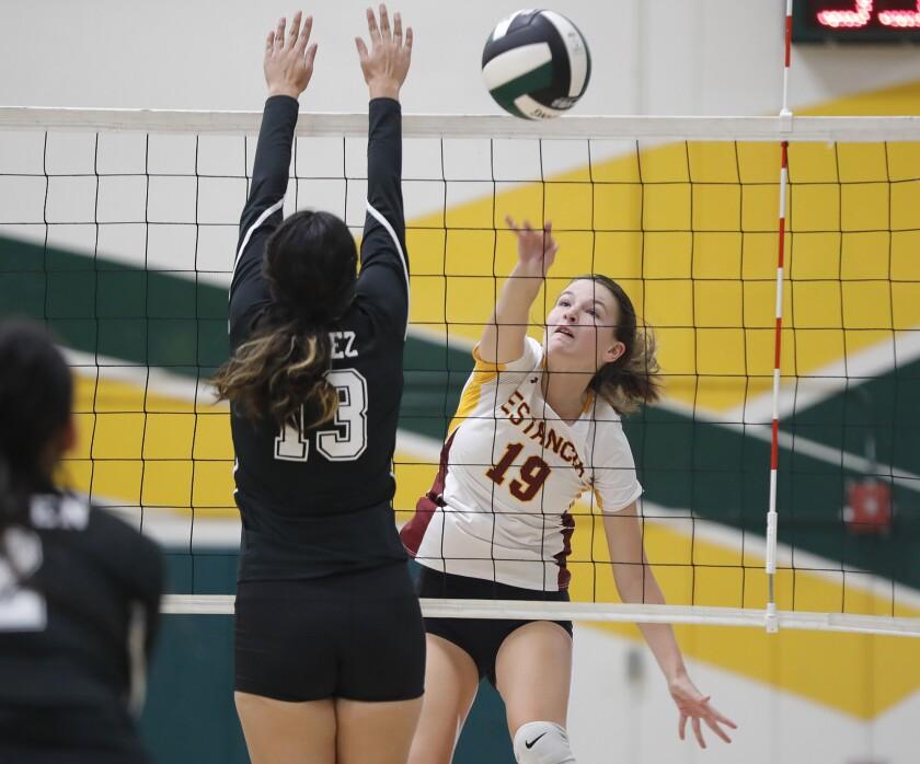 Estancia's Joanna Santosuosso smashes the ball past a Rancho Alamitos blocker in girls' varsity volleyball on Thursday.