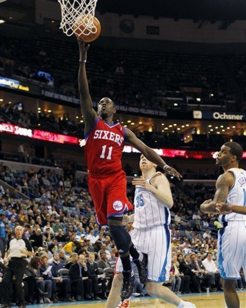 Philadelphia 76ers point guard Jrue Holiday (11) drives to the basket in front of New Orleans Hornets center Chris Kaman (35) in the first half of an NBA basketball game in New Orleans, Wednesday, Jan. 4, 2012. (AP Photo/Gerald Herbert)