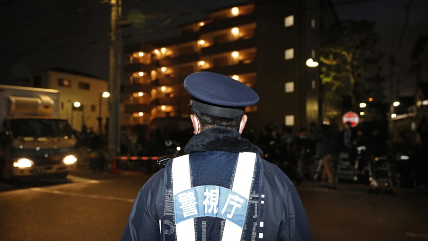 A police officer guards the entrance of the Tokyo Detention Center where former Nissan chairman Carl