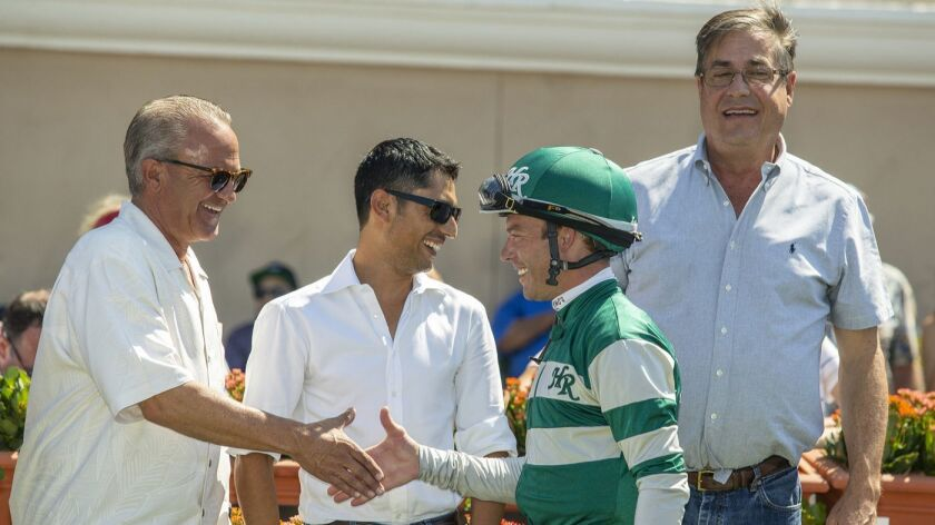 In a photo provided by Benoit Photo, owner Kosta Hronis, left, celebrates with assistant trainer Jua