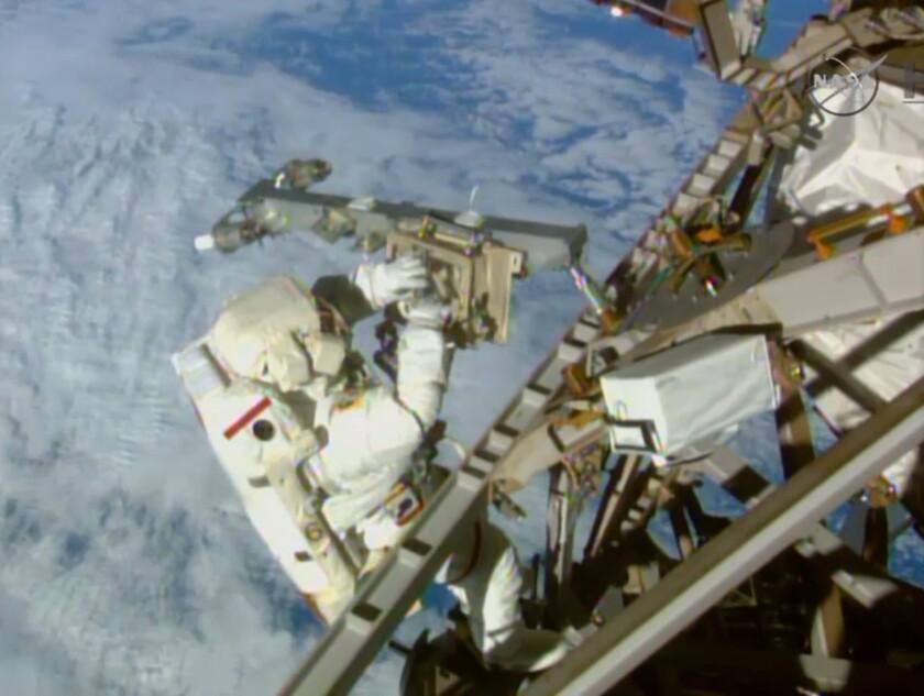 En imagen tomada de un video proporcionado por la NASA, el astronauta Terry Virts instala una antena y un boom durante una caminata espacial afuera de la Estación Espacial Internacional. El viernes 19 de febrero de 2016, la NASA anunció que recibió una cifra record de solicitudes para su próxima generación de astronautas. (AP Photo/NASA-TV)
