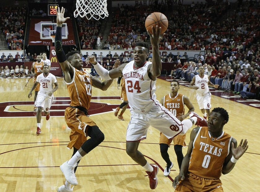 Oklahoma guard Buddy Hield (24) goes to the basket between Texas guard Kerwin Roach Jr. (12) and guard Tevin Mack (0) in the first half of an NCAA college basketball game in Norman, Okla., Monday, Feb. 8, 2016. (AP Photo/Sue Ogrocki)