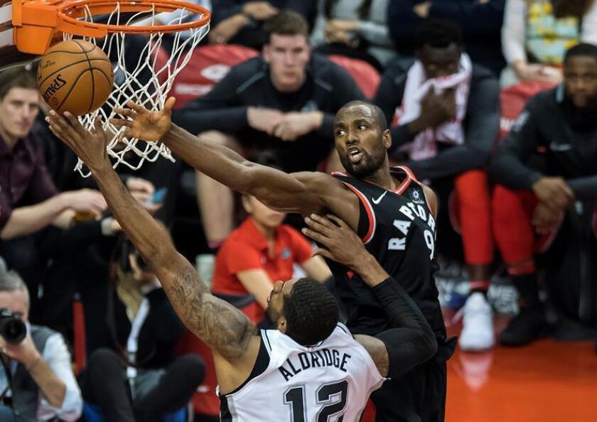 LaMarcus Aldridge (i) de Spurs disputa el balón ante Serge Ibaka (d) de Raptors durante un partido de baloncesto de la NBA en Toronto (Canadá). EFE/Archivo