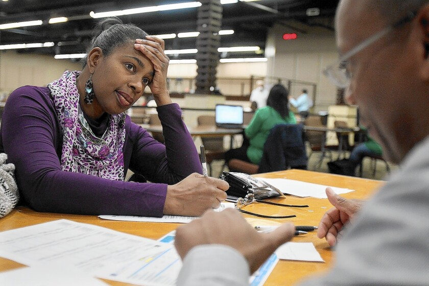 Denise Paul, left, signs up for health coverage with an enrollment counselor at an event this month at Faithful Central Bible Church in Inglewood.