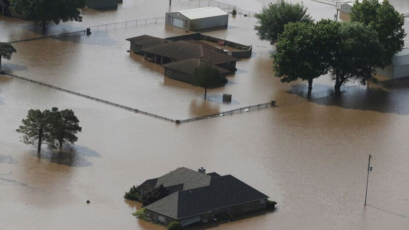 Homes are flooded on the Arkansas River in Tulsa, Okla., on Friday, May 24, 2019. The threat of pote