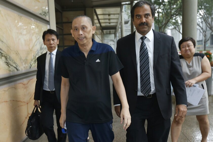 Tan Seet Eng, also known by the nickname of Dan Tan, front left, leaves the supreme court in Singapore Wednesday, Nov. 25, 2015 in Singapore. Tan, who was detained for more than two years under suspicion of being the mastermind behind a global soccer match-fixing syndicate, was ordered to be released on Wednesday by the country's highest court, which ruled he was being held unlawfully. (AP Photo/Ernest Chua/Today via AP)