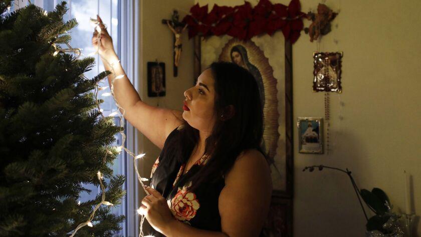 SANTA CRUZ, CA-DECEMBER 16, 2018: Gabriela Cruz decorates her family's Christmas tree at her home in