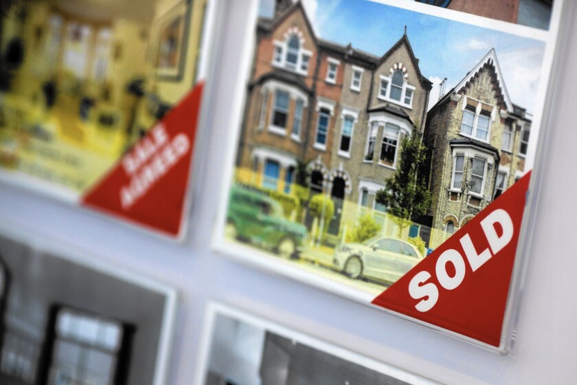 """A """"sold"""" sign sits on a photo of a residential property in a real estate agent's window display in London. In Europe, it's practically unheard-of to move into a place with a fully outfitted kitchen."""
