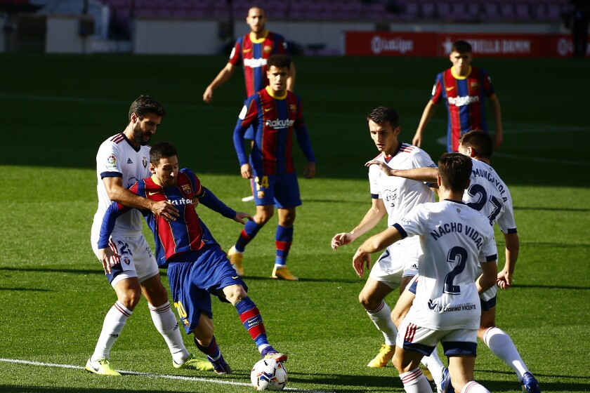 Barcelona's Lionel Messi, second left, vies for the ball with Osasuna's Raul Navas, left, during the Spanish La Liga soccer match between FC Barcelona and Osasuna at the Camp Nou stadium in Barcelona, Spain, Sunday, Nov. 29, 2020. (AP Photo/Joan Monfort)