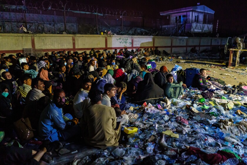 Afghan refugees crouch in a group as British military secure the perimeter outside the Baron Hotel in Kabul.