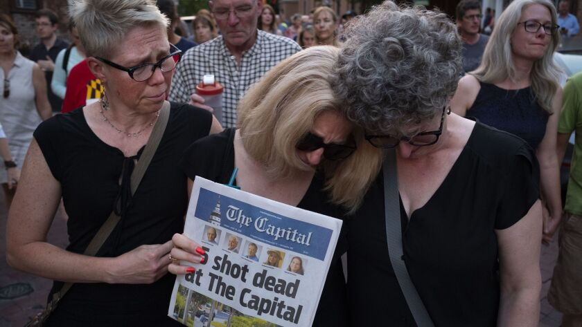 Andrea Chamblee, center, wife of shooting victim and reporter John McNamara, marches in a vigil held in downtown Annapolis, Md., on Friday.