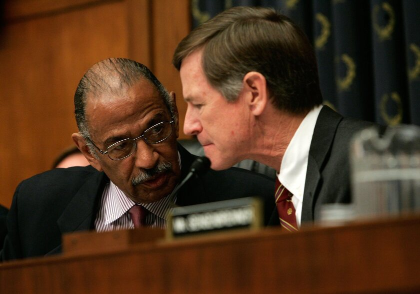 Rep. Lamar Smith (R-Texas), right, with Rep. John Conyers (D-Mich.) in 2007. Smith has hacked away at climate change funding but doesn't want to say so.
