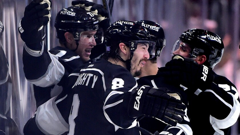 Kings center Jeff Carter, left, celebrates with teammates, including defenseman Drew Doughty, after scoring the winning goal against the Predators in overtime.