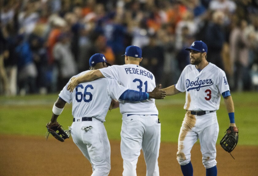 Yasiel Puig, left, Joc Pederson and Chris Taylor celebrate as the Dodgers win game 6 of the World Series 3-1 at Dodger Stadium.