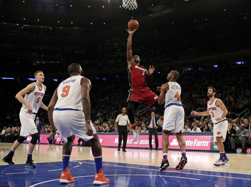 Miami Heat guard Dwyane Wade (3) drives to the basket past New York Knicks guard Arron Afflalo (4) during the first half of an NBA basketball game at Madison Square Garden on Friday, Nov. 27, 2015, in New York. (AP Photo/Adam Hunger)
