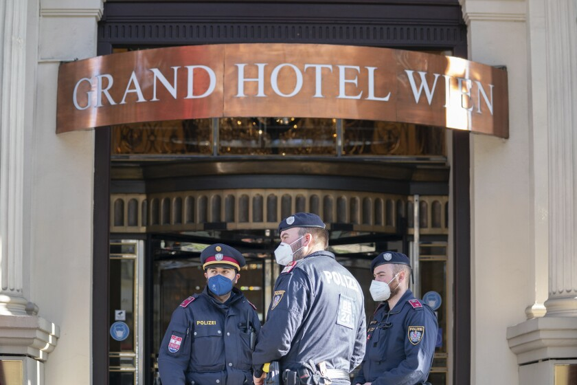 Police officers stay in front of the 'Grand Hotel Wien' in Vienna, Austria, Friday, April 9, 2021 where closed-door nuclear talks with Iran take place. Diplomats meeting in Vienna assess progress of three days of talks aimed at bringing the United States back into the nuclear deal with Iran. (AP Photo/Florian Schroetter)
