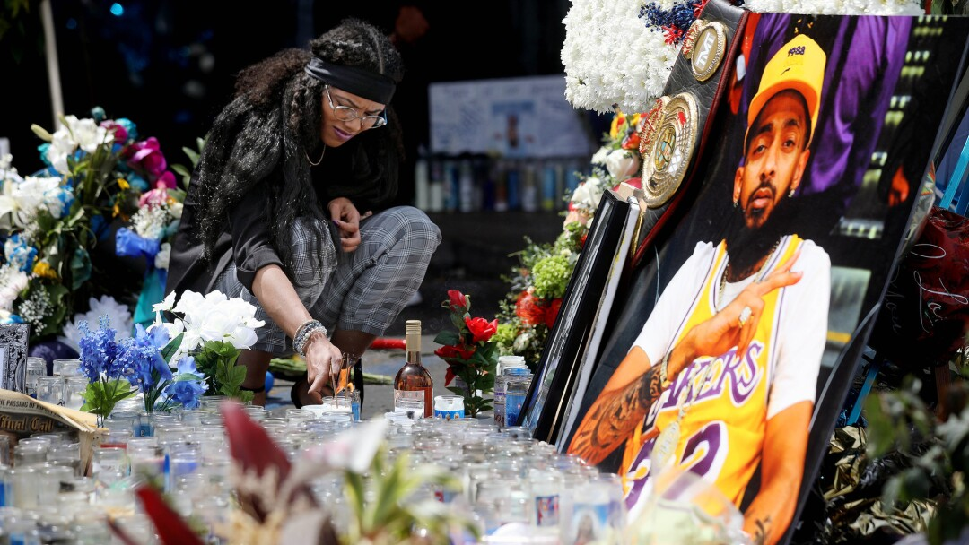 Corina Samarco of Ypsilanti, Mich., lights a candle in the parking lot of the Marathon Clothing Company before the start of the Nipsey Hussle Celebration of Life procession on April 11.