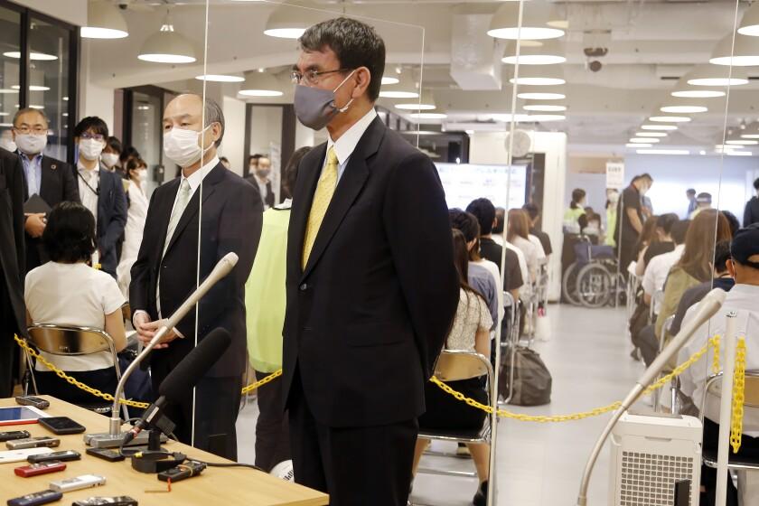 El ministro de vacunación contra el COVID-19 Taro Kono, centro, y Masayoshi Son, CEO de la tecnológica japonesa SoftBank Group Corp., izquierda, hablan con la prensa después de visitar un centro de vacunación instalado por la empresa, martes 15 de enero de 2021 en Tokio. (AP Foto/Yuri Kageyama)
