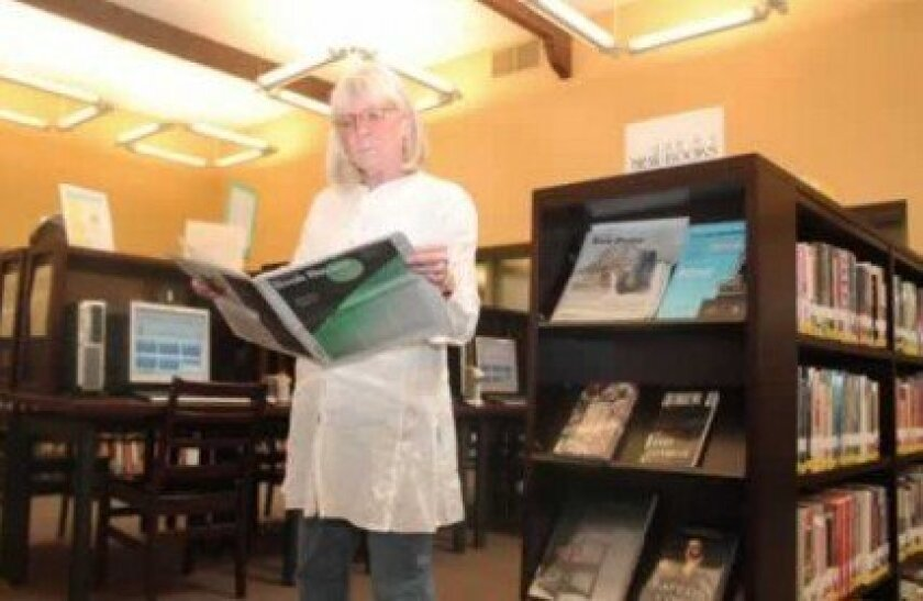 La Jolla riford Library's head librarian, Catherine Greene, leafs through a recent edition of the New York Times books section, which is available for readers to review before making selections. Pat Sherman