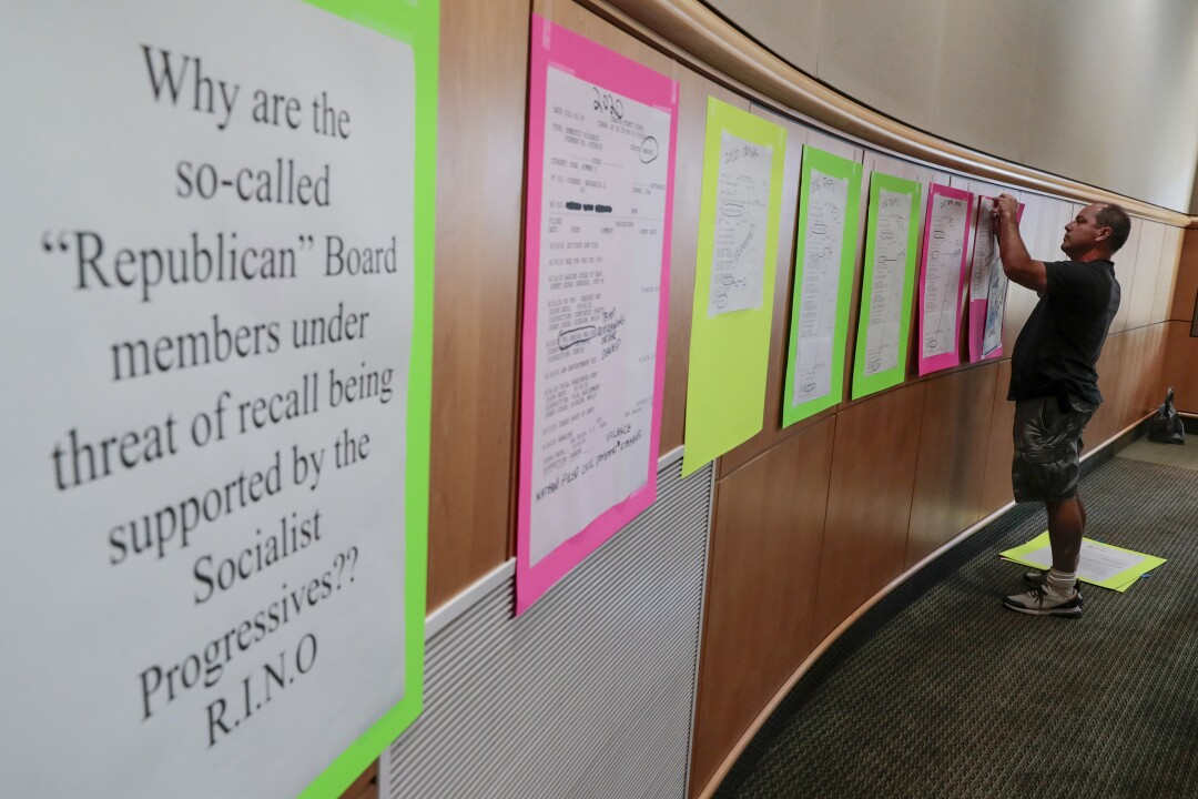 Richard Gallardo tapes posters showing traffic tickets, court documents and social media posts by Nathan Pinkney