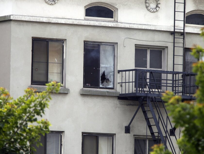 A puff of smoke rises from the window as members of the San Diego Police Department respond to a reportedly suicidal gunman holed up in an apartment building (window with riped shade) in the 900 block of Broadway in downtown San Diego, California.