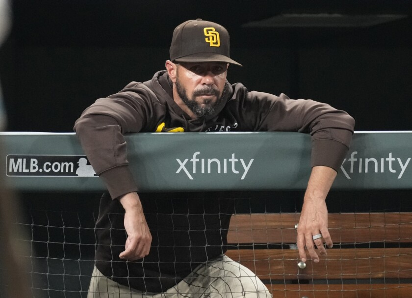Former Padres manager Jayce Tingler leans over the dugout rail during August game at Coors Field.