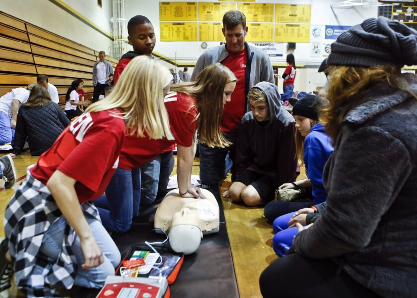 Oceanside teacher Doug Musgrove (top center) looks on as Callie Zellers demonstrated CPR techniques during training for teenagers and their parent at the free youth heart screening at El Camino High School on Sunday. Hundreds of children showed up the free screening administered by the Eric Paredes Save a Life Foundation. The nonprofit Eric Paredes foundation was founded to honor a 15-year-old Steele Canyon High School student who lost his life to sudden cardiac arrest in 2009. Photo by Don Boomer