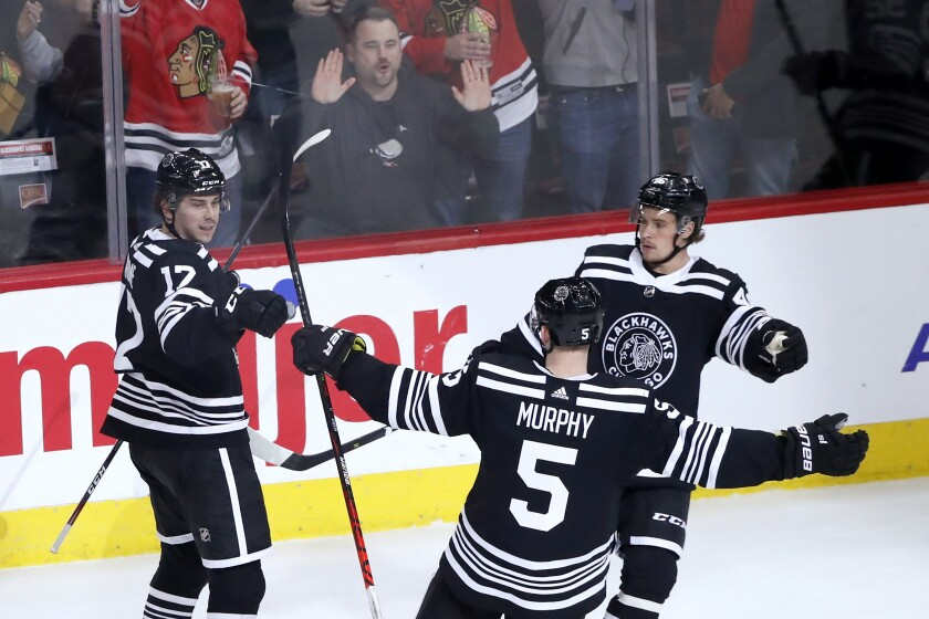 Chicago Blackhawks' Dylan Strome (17) celebrate his second goal of the night with Connor Murphy (5) and Lucas Carlsson during the second period of the team's NHL hockey game against the Anaheim Ducks on Tuesday, March 3, 2020, in Chicago. (AP Photo/Charles Rex Arbogast)