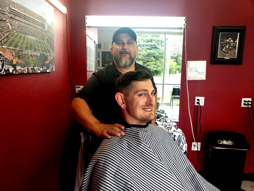 Wes Heryford, 42, gives J Farr, 28, a haircut at Butte House Barber Shop in Yuba City. Farr drove more than 600 miles from Olympia, Wash., to get his hair trimmed while barbershops elsewhere are closed.