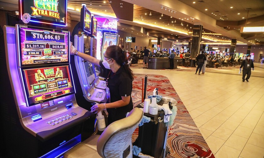 Environmental services worker Marcela Averion sanitizes a slot machine on opening day at Sycuan Casino on May 20.