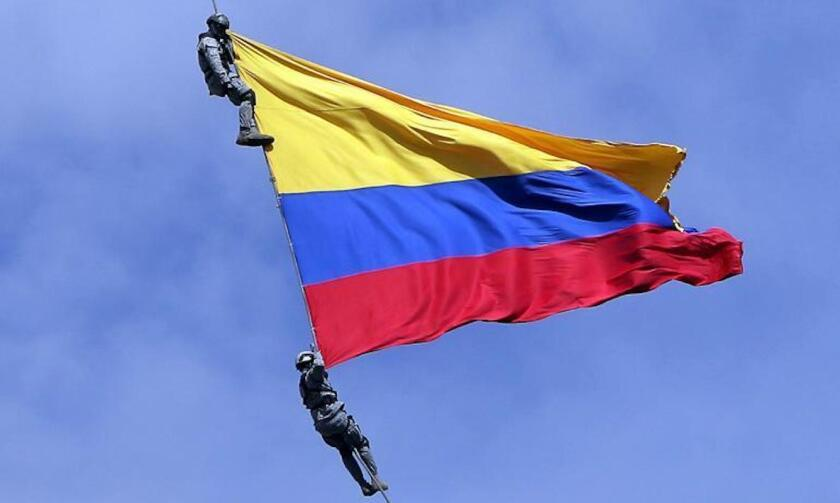 Dos soldados de la fuerza aérea de Colombia cuelgan de un helicóptero con una bandera colombiana durante la 'Feria de las Flores' en Medellín. Ambos fallecieron al reventarse el cable.