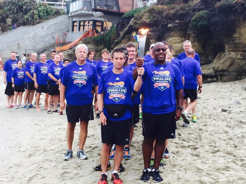 Special Olympics Law Enforcement Torch Run participants present the torch at La Jolla Cove Saturday afternoon, July 18. A break in the flash floods that pummeled San Diego provided an opportunity for runners to get off their bus for a photo opportunity at the Cove. Nathan Fletcher, an executive wit