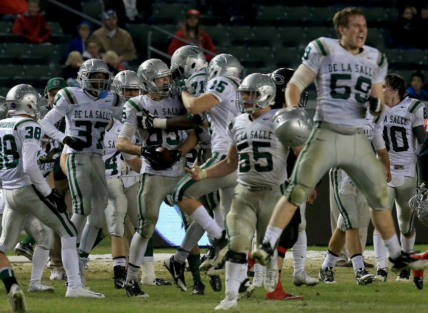 De La Salle players celebrate after an interception against Corona Centennial in the 2014 Open Division state bowl game.