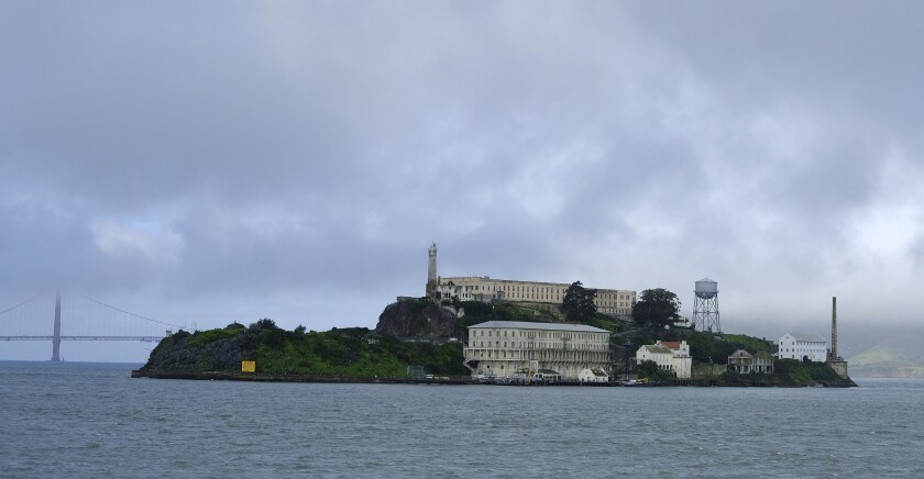 """FILE - In this March 6, 2019, file photo, is Alcatraz Island in San Francisco. Alcatraz Island will reopen its outdoor areas to the public next week after being closed for five months due to the pandemic. The Mercury News reports Thursday, Aug. 13, 2020, the island that once housed Al Capone and George """"Machine Gun"""" Kelly will reopen Monday but will be an outdoor-only experience, to reduce the risk of spreading COVID-19. (AP Photo/Eric Risberg, File)"""