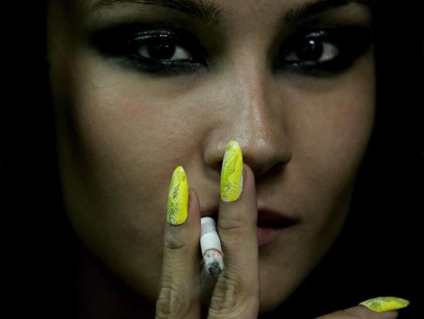 Una modelo fuma un cigarro entre bastidores antes del desfile de BabyPhat en el Radio City Music hall durante la Semana de la Moda de Nueva York, Estados Unidos, el sábado 10 de septiembre de 2005. EFE/Archivo