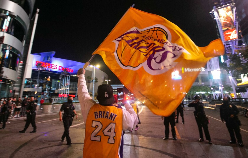 A fan in a Kobe Bryant jersey waves a Lakers flag in downtown Los Angeles after the team won the NBA championship Oct. 11