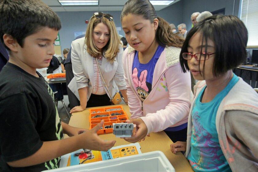 Laurel Elementary School fifth graders Espen Garrett, left, Ariana Perez, center right, and fourth grader Giannamae Felix show Vanir Foundation board member Teri Cruze their work in a robotics class at the school Friday.