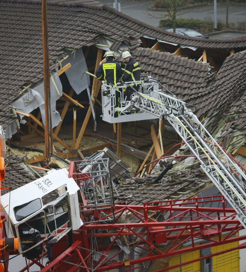 Firefighters are watching out the site where a crane collapsed and crashed into a supermarket in Bad Homburg, Germany, Wednesday, Dec. 11, 2013. Quoting local police, the German news agency dpa reported that several people had been injured but didn't provide further details. (AP Photo/dpa, Frank Rumpenhorst)