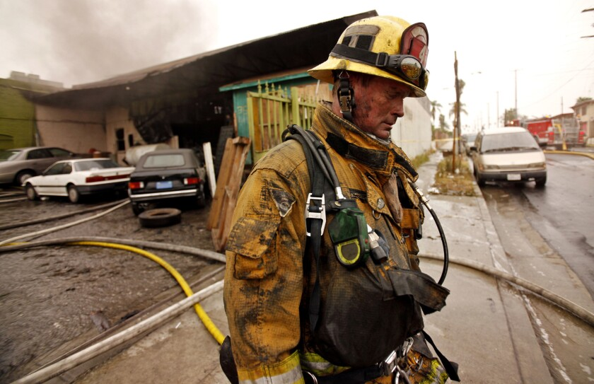 A Los Angeles Fire Department firefighter mops up after a 2010 fire in Boyle Heights.