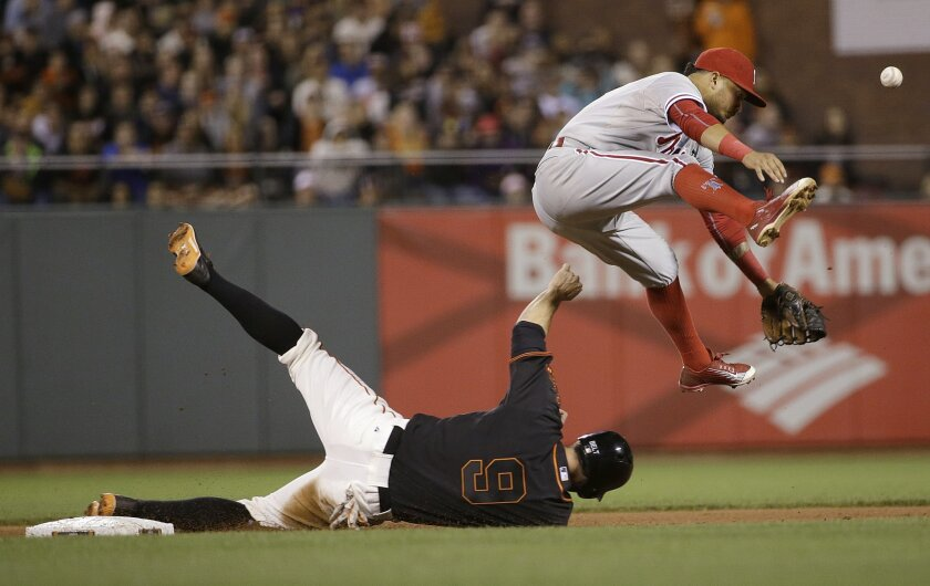 Philadelphia Phillies shortstop Freddy Galvis, top, loses the ball after forcing out San Francisco Giants' Brandon Belt (9) at second base on a ball hit by Brandon Crawford during the seventh inning of a baseball game in San Francisco, Saturday, July 11, 2015. (AP Photo/Jeff Chiu)
