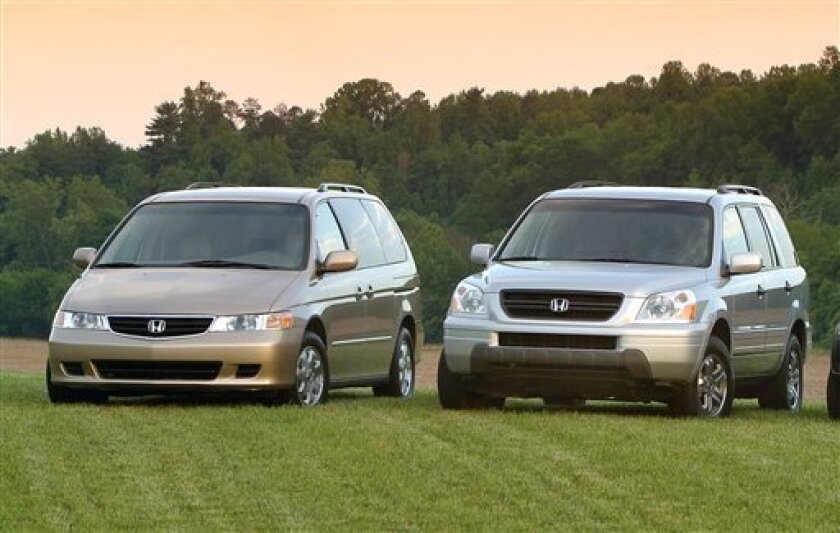 FILE - A 2003 Honda Odyssey and 2003 Honda Pilot are shown in a undated Honda Motor Company file photo. Safety regulators in the U.S. are investigating complaints that older Honda Odyssey Minivans and Pilot SUVs can roll away after drivers have removed the ignition key. The probe by the National Highway Traffic Safety Administration affects more than 577,000 vehicles from the 2003 and 2004 model years with automatic transmissions. (AP Photo/Honda Motor Company, File)