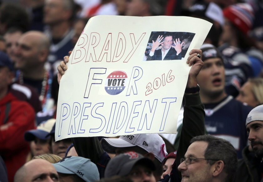 """FILE - In this Oct. 25, 2015 file photo, a New England Patriots fan holds a sign that supports Patriots quarterback Tom Brady for president during an NFL football game against the New York Jets in Foxborough, Mass. GQ magazine asked Brady, its 2015 Man of the Year, if he's ever considered making a play for the White House or at least for governor of Massachusetts. Brady said. """"There is a 0.000 chance of me ever wanting to do that."""" (AP Photo/Steven Senne, File)"""