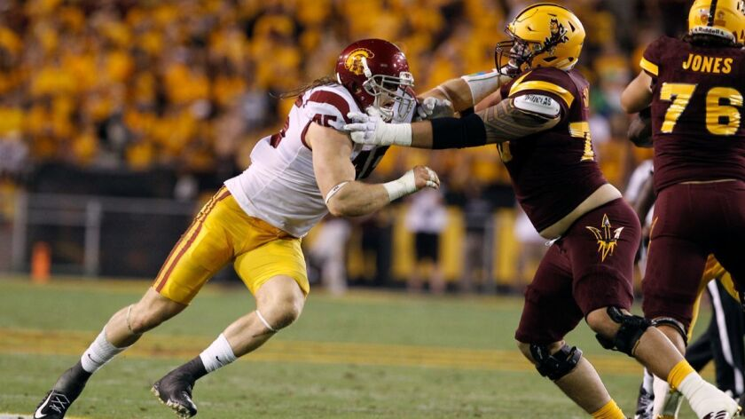 USC linebacker Porter Gustin (45) battles Arizona State offensive lineman Cohl Cabral during the second half on Saturday.